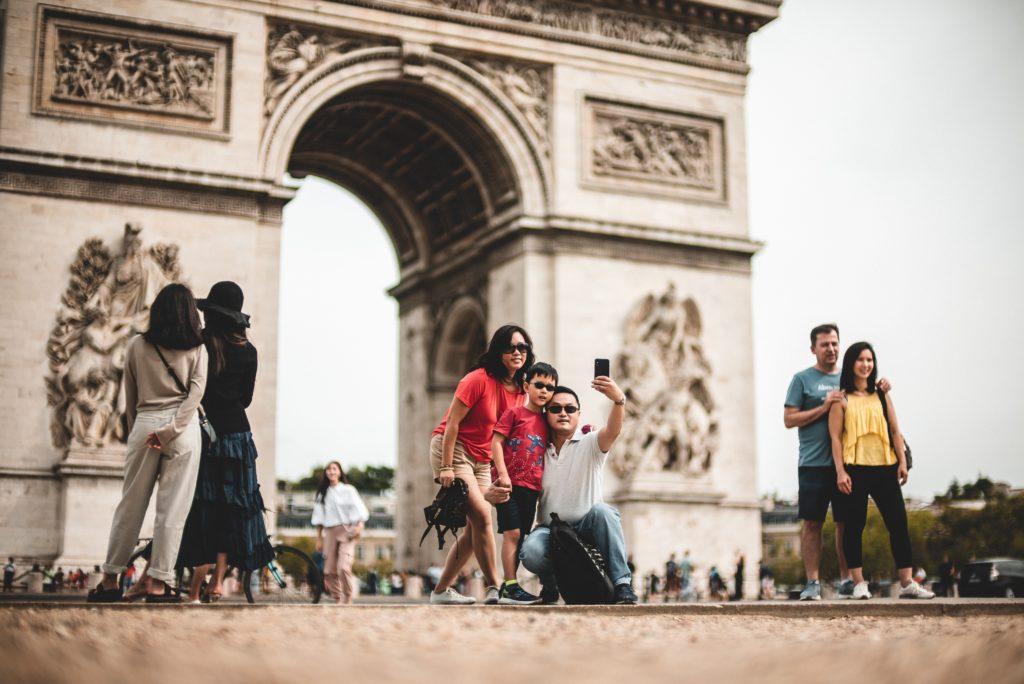 Touristes se prennent en photo devant l'Arc de Triomphe
