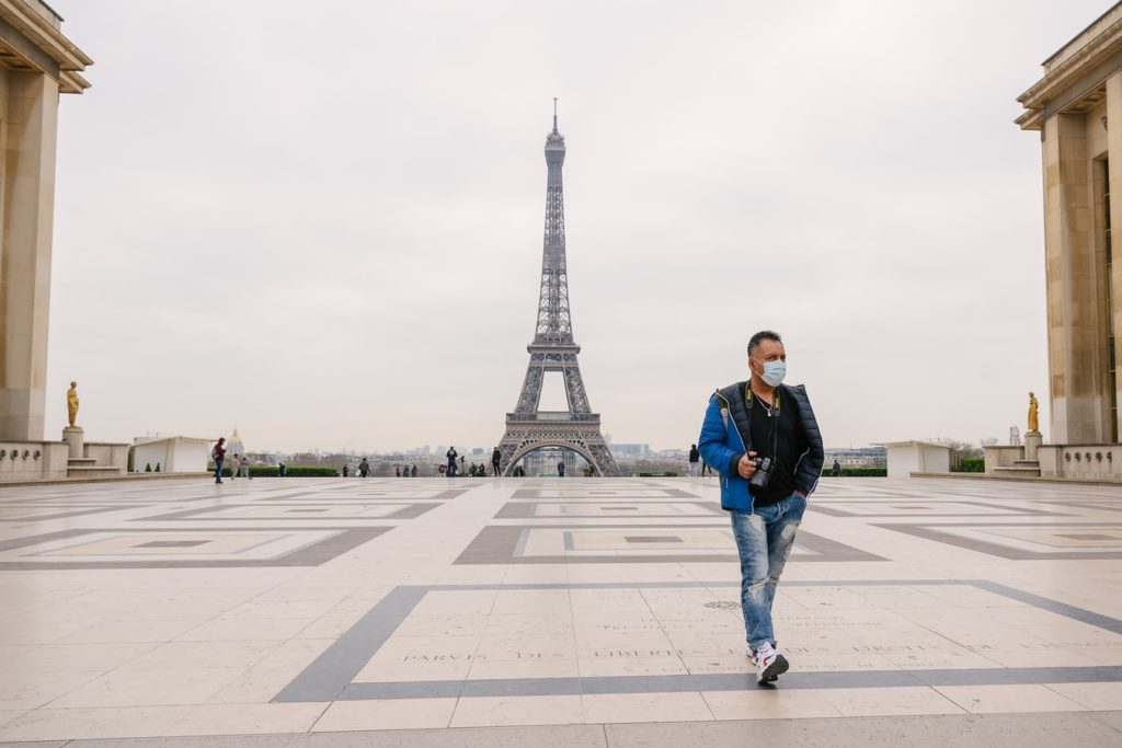 Touriste masqué devant Tour Eiffel